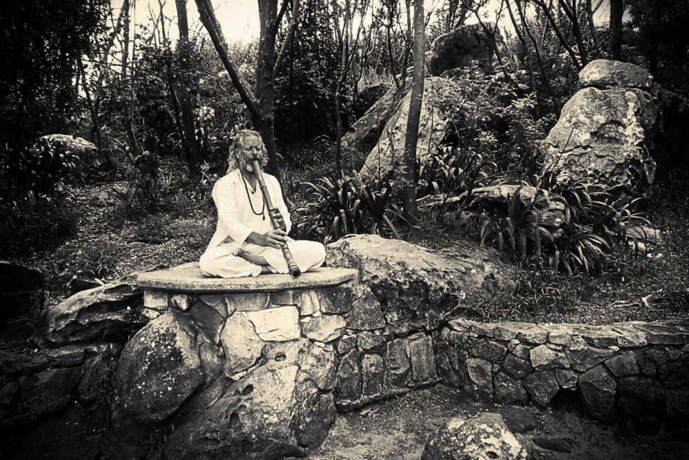 Adrian Freedman plays shakuhachi in a garden B&W. Silvermine National Park, Cape Point, South Africa. Photo: Martyn John Taylor projects