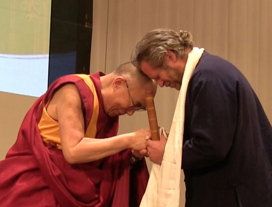 The Dalai Lama holding hands and shakuhachi with Adrian Freedman. Credit: Christopher Fryman