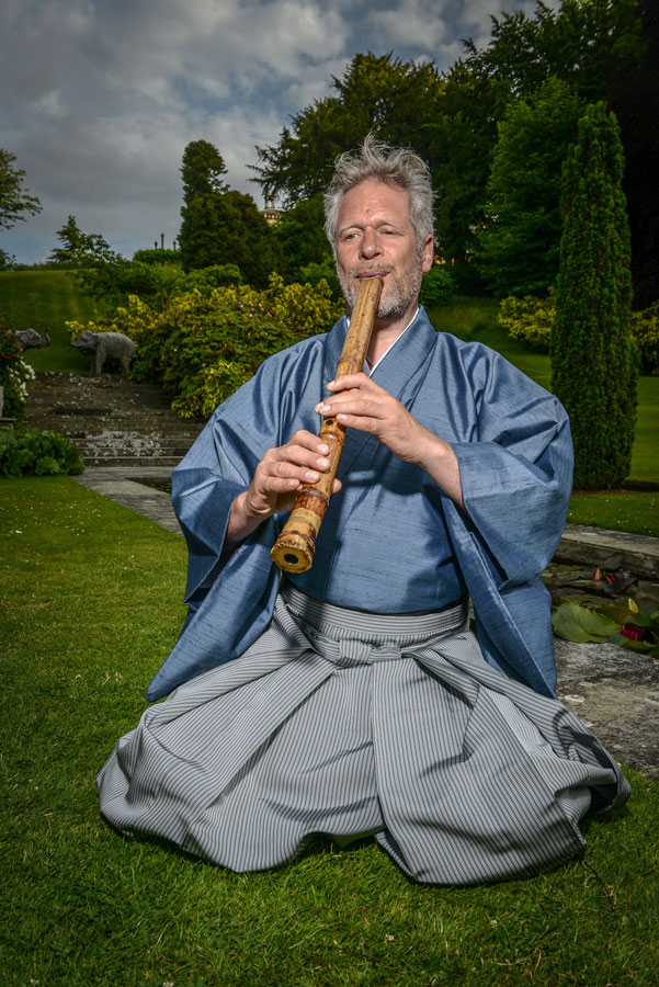 Adrian Freedman playing shakuhachi wearing blue kimono press