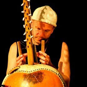 Black and Yellow photo of Ravi playing kora slim